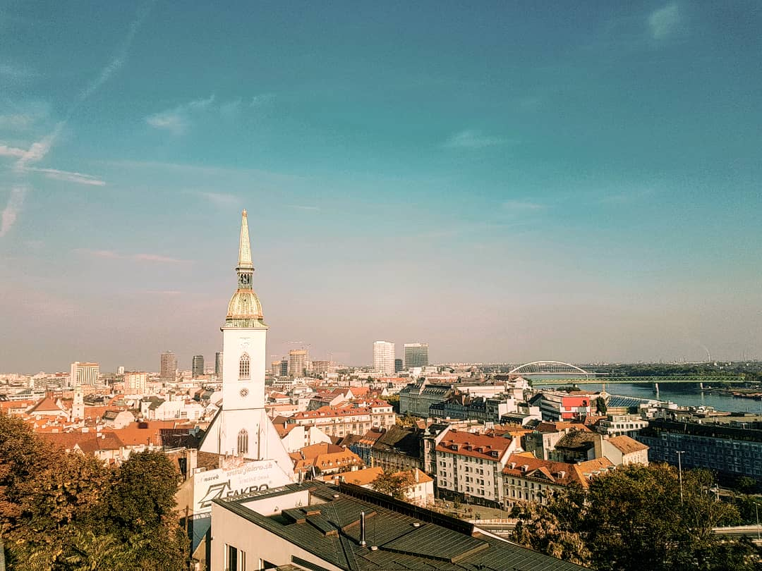 A cityscape with a river in the corner and baroque style church - One and Two Day Itineraries To Bratislava + First Timer's Guide: Written By Locals!